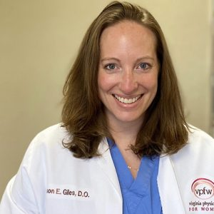 Dr. Giles smiling with shoulder length brown hair in blue scrubs and white doctors coat that says her name and Virginia Physicians for Women