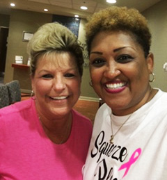 A woman in pink scrubs hugs and smiles with a woman in a white pink ribbon t-shirt