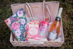 Pink Michael Kohrs purse gift basket with flowered notebook, pink popcorn, a plastic VPFW wine cup and pink lid, and a bottle of sparkling rose.