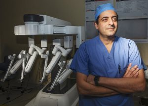 VPFW's Dr. Ramzi Aboujaoude, urogynecologist wearing blue scrubssmiles with arms crossed in front of robotics surgery equipment for Chesterfield Observer