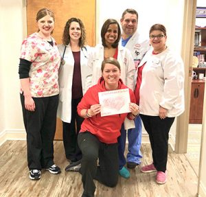 Dr. Clary and VPFW physicians and staff at VPFW's office at Henrico Doctors' Hospital wearing red accents with their white coats