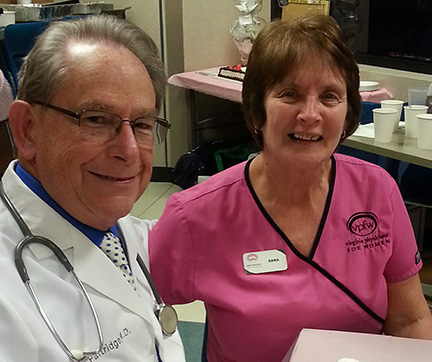 VPFW Phone nurse Sara Walsh in pink scrubs sits smilig with Dr. Partridge in white coat and stethoscope