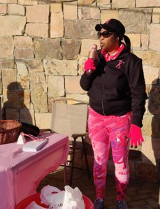 Woman in pink gloves, pants, and pink ribbon jacket speaking into a pink microphone