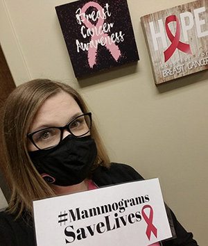 Woman with mask and glasses holding a sign that says mammograms save lives with a poster that says breast cancer awareness behind her