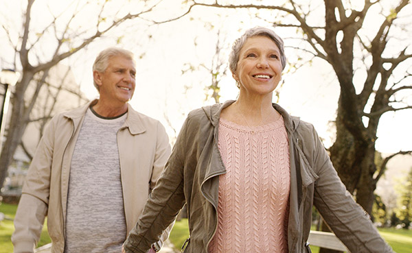Woman in pink sweater and jacket smilingand feeling free from prolapse with husband behind her outside in a park