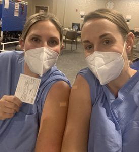 Dr. Schnatz and Dr. Hempel, smiling under their masks, showing their band-aided arms and COVID-19 vaccine cards