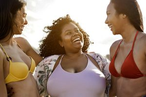 Girls laughing at the beach talking about how to prevent yeast infections
